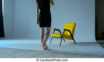 Slim girl in black dress sits down on a Chair in the Studio...