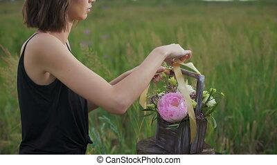 Slim girl in black dress works of flowers at sunset