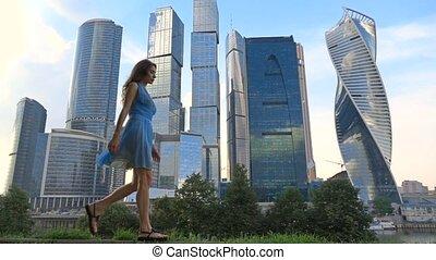 Slim girl in blue dress walking against modern skyscrapers, super slow motion video, 250 fps