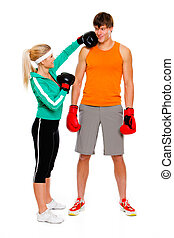 Slim girl in boxing gloves punching man isolated on white