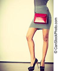 Slim girl in gray skirt with red handbag