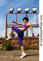 Slim girl in purple clothes dancing on the roof at summer day