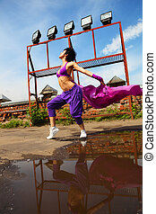Slim girl in purple clothes dancing with kerchief on the roof at summer day