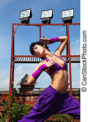 Slim girl in purple clothes poses on the roof at summer day