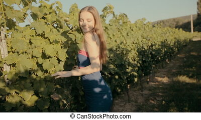 Slim girl in strapless dress posing in rows of vineyards