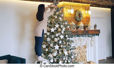 Slim girl in sweater and jeans is decorating beautiful New Year tree touching balls and stars and creating perfect design. Decorated fireplace and lights are visible.