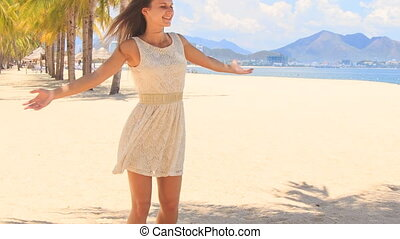 slim girl in white frock swings with hands aside on beach