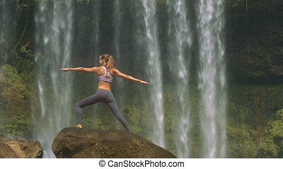 Slim Girl Poses on Round Rock against Waterfall