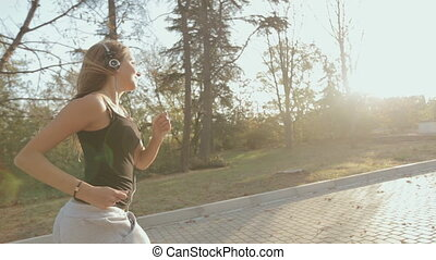Slim girl runing through the park and listening to music...