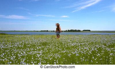 slim girl runs on buckwheat field to distant lake