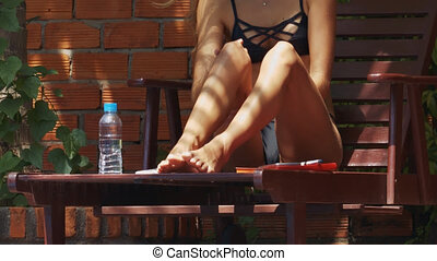 Slim Girl Smears Legs and Thighs with Sunscreen - closeup...