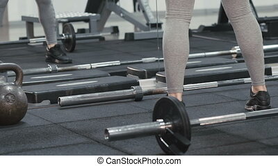 Slim girl stretching her legs' muscles with exercise in the modern gym