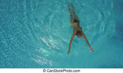 slim girl swims in blue swimming pool