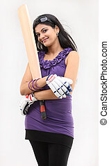 Slim girl with cricket bat standing in violet dress standing...