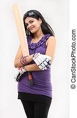 Slim girl with cricket bat standing in violet dress standing...