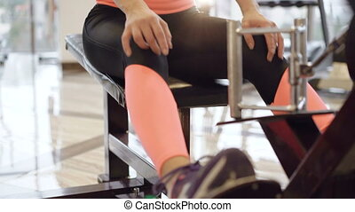 Slim girl workout with simulator for muscles in the gym