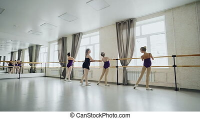Slim girls are learning backward bends practising ballet...