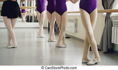 Slim girls' legs in tights are doing battement tendu during...