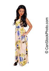 Slim Indian woman standing in dress.