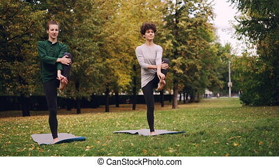 Slim ladies are exercising outdoors in park standing on one...