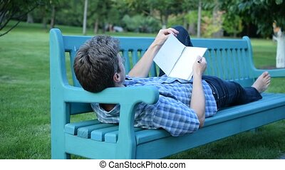 Slim man lying on a bench and writing in notepad