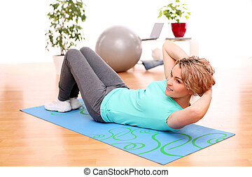 slim mid aged woman do fitness exercises at home - slim mid...