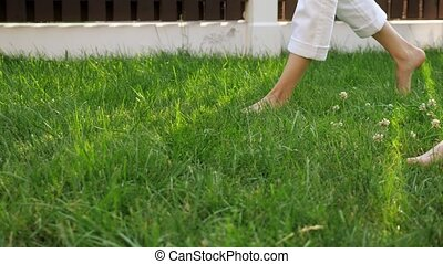slim mother and little boy legs walk barefoot on green lawn