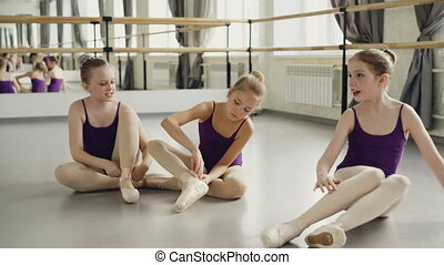 Slim pretty children are wearing ballet slippers on studio...