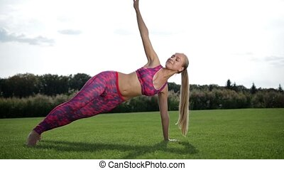 Slim pretty woman doing side plank on green grass