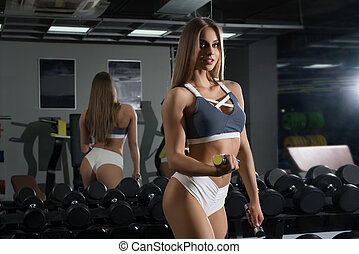 Slim sexy fitness trainer posing with a dumbell - Slim sexy...