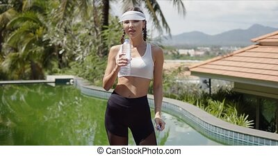 Strong female in sportswear enjoying fresh cold water and looking at camera while standing on poolside during break in fitness training