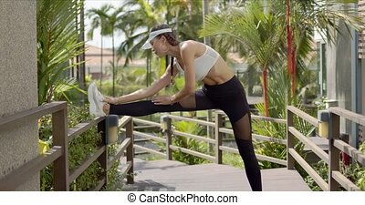 Strong female in sportswear stretching leg on railing of wooden path during fitness workout on sunny day on tropical resort