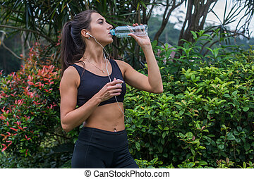Slim sporty girl drinking water. Fitness young woman taking a break after training in park.
