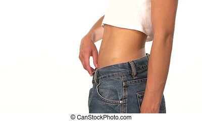 Slim, sporty girl in big jeans, showing her lose weight and spinning, on white background, close up