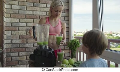 Slim sporty woman making a homemade green detox smoothie