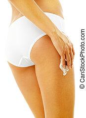 Slim tanned woman applying cosmetics