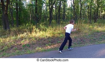 Slim teenager boy is running on paths and trails in the forest.
