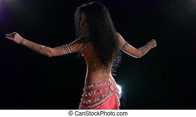 Slim torso of a beautiful belly dancer on a black, back light, slow motion