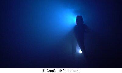 Slim woman dancing striptease view in blue smoke