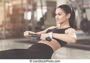 Slim woman doing sit ups in gym.