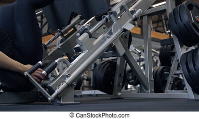 slim woman in black sportswear use leg press machine in gym.