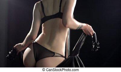 Slim woman in black underwear dancing in the dark room