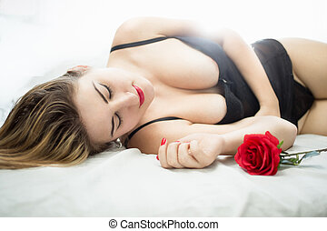 slim woman in corset lying in bed with red rose - Beautiful...