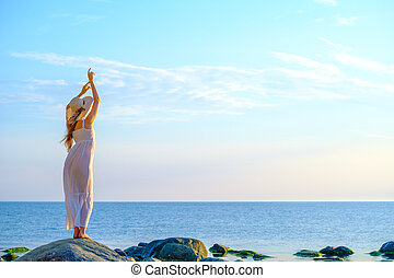 Slim woman in dress near sea