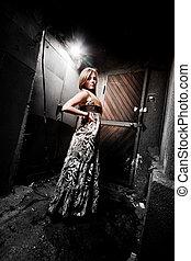 Slim woman in dress posing on courtyard at night