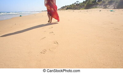 Slim Woman in Long Red Dress Leaves Footprints on Wet Sand