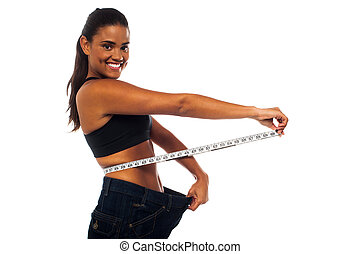 Young woman measuring waist with a white measuring tape