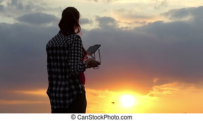 Slim woman operates a panel to control a drone at sunset
