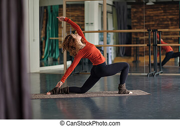 Slim woman practice in yoga studio doing Anjaneyasana
