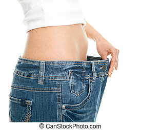 Slim woman pulling oversized jeans. Weight loss concept....
